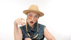 De modellen in hoed met twee vlechten en glassess, kijkt als een cowboymeisje stock videobeelden