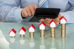 De Modellen van zakenmanwith calculator in Front Of Coins And House Royalty-vrije Stock Afbeelding