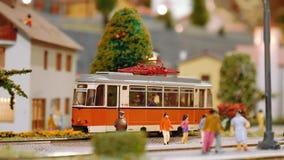 De modeltram komt dan twee treinen overgaat door op diorama aan stock videobeelden