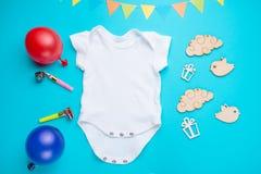 De modelvlakte legt wit kinderenoverhemd met speelgoed en ballen op een blauwe achtergrond Lay-out voor het ontwerp en de plaatsi royalty-vrije stock foto's