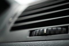 De moderne automobielautoairconditioning (de opening van de autoventilatie) met gradiënt maakte controlewiel in zwarte kleur rond stock afbeeldingen