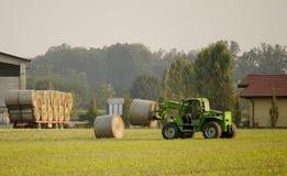 De moderne balen van het tractor bewegende hooi Stock Foto's