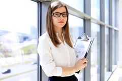 De moderne bedrijfsvrouw die en documenten in het bureau met exemplaar bevinden zich houden plaatst gebied uit elkaar Royalty-vrije Stock Afbeeldingen