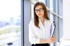 De moderne bedrijfsvrouw die en documenten in het bureau met exemplaar bevinden zich houden plaatst gebied uit elkaar Royalty-vrije Stock Foto