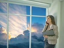 De moderne bedrijfsvrouwen gebruiken mobilofoon terwijl het bekijken idyllisch s stock foto's