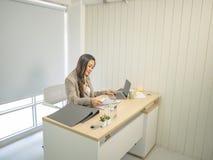 De moderne bedrijfsvrouwen nemen ernstig en het werken aan haar bureau royalty-vrije stock fotografie