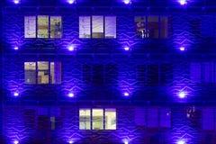 De moderne blauwe verlichte bouw van het glasbureau fasade stock foto's
