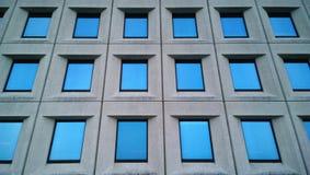 De moderne bouw die van commercieel centrum met mooie glasvensters, op de blauwe hemel wijzen Stock Afbeelding