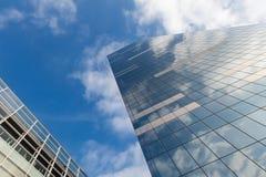 De moderne bureaubouw op hemelachtergrond met wolkenbezinning Royalty-vrije Stock Afbeeldingen