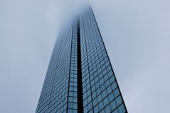 De moderne bureaubouw van glas kijkt als een messenblad in mist Stock Foto