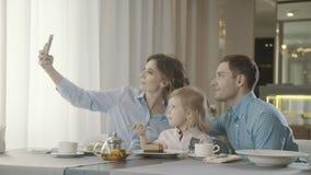 De moderne familie met een klein kind in een familierestaurant eet dessert stock footage