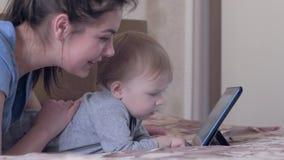 De moderne familievrije tijd, aardige zuigelingsjongen met jonge mum heeft pret die met aanrakingstablet op bed thuis liggen stock video