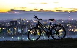 De moderne fiets die van de sportenstad zich alleen over de achtergrond van de nachtstad bevinden stock fotografie