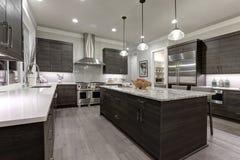 De moderne grijze keuken kenmerkt donkergrijze vlakke voordiekabinetten met witte kwartscountertops in paren worden gerangschikt stock afbeelding