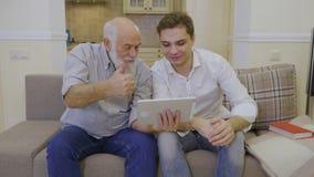 De moderne grootvader toont video aan zijn kleinzoon in Internet op digitale tablet stock footage