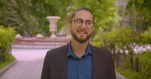 De moderne hipsterzakenman loopt aan camera en glimlacht in het die gelukkig en positief in park zijn stock footage