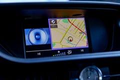 De moderne ingebouwde navigator in de auto in het paneel met het beeld van de kaart op de vertoning en stemcontrole bedekt de rou stock afbeeldingen