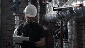 De moderne ingenieur in ketelruim, neemt nota's over een tablet voor documenten stock footage