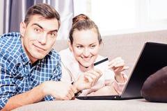 De moderne jonge familie maakt tot aankopen online Leda op bank gebruikend laptop, betaling door creditcard Emotioneel gezicht royalty-vrije stock afbeeldingen