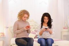 De moderne jonge meisjes gebruiken smartphones en doen persoonlijke dingen, sitti Royalty-vrije Stock Foto