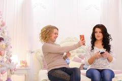 De moderne jonge meisjes gebruiken smartphones en doen persoonlijke dingen, sitti Stock Afbeelding