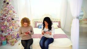 De moderne jonge meisjes gebruiken smartphones en doen persoonlijke dingen, zittend op bed in heldere slaapkamer met feestelijke  stock footage