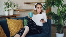 De moderne jonge vrouw rust op comfortabele bank thuis met smartphone, kop thee en hoofdtelefoons Het meisje luistert stock video