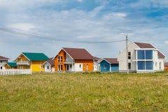 De moderne kleine gekleurde huizen bouwden het platteland tegen een blauwe hemel met wolken in stock foto