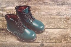 De moderne laarzen van het jongens` s leer op donkere houten achtergrond Stock Foto's