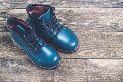 De moderne laarzen van het jongens` s leer op donkere houten achtergrond Stock Afbeeldingen