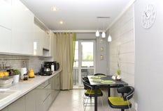 De moderne lichte keuken met het ingebouwde meubilair Binnenlands stock afbeeldingen