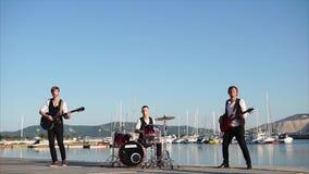 De moderne musici voeren een muzikale samenstelling op instrumenten dichtbij het overzees uit stock videobeelden