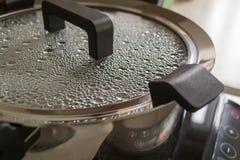 De de moderne pot of pan van de metaalsoep met zwarte handvatten op een inductiefornuis De dalingen van kokend water zijn op binn royalty-vrije stock afbeelding