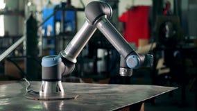 De moderne robotachtige apparatenwerken bij een fabriek, die zich op een lijst bewegen stock videobeelden