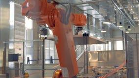 De moderne robotachtige wapenwerken in een fabrieksvloer stock videobeelden