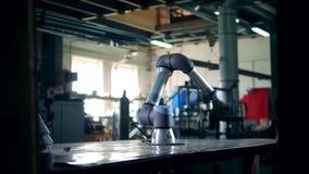 De moderne robotachtige wapenwerken met een toestel op een lijst stock footage