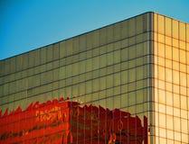 De moderne rode die bouw in de gouden bouw wordt weerspiegeld Stock Fotografie