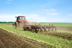 De moderne rode tractor die van technologie een groen landbouwgebied in de lente op het landbouwbedrijf ploegen Maaimachine het z Stock Afbeeldingen