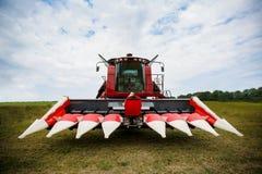 De moderne rode tractor die van technologie een groen landbouwgebied in de lente op het landbouwbedrijf ploegen Maaimachine het z Stock Fotografie