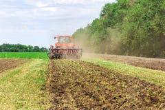 De moderne rode tractor die van technologie een groen landbouwgebied in de lente op het landbouwbedrijf ploegen Maaimachine het z Royalty-vrije Stock Foto's