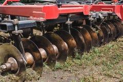 De moderne rode tractor die van technologie een groen landbouwgebied in de lente op het landbouwbedrijf ploegen Maaimachine het z Stock Foto's