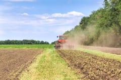 De moderne rode tractor die van technologie een groen landbouwgebied in de lente op het landbouwbedrijf ploegen Maaimachine het z Royalty-vrije Stock Afbeeldingen