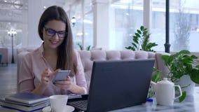 De moderne slimme technologieën, de gelukkige vrouw van de restaurantmanager fotografeerden op celtelefoon tijdens het werk bij l stock video