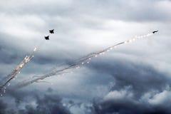 De moderne straalvechter steekt een reeks gloed op de blauwe hemel in brand Wolkencondensatie op de vleugels stock afbeelding