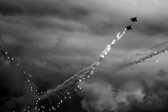 De moderne straalvechter steekt een reeks gloed op de blauwe hemel in brand Wolkencondensatie op de vleugels royalty-vrije stock foto's