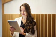 De moderne technologieën van het modieuze vrouwengebruik Jonge meisjestribunes met tablet Stock Afbeelding