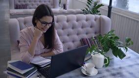 De moderne technologie in onderwijs, mooi meisje in oogglazen die laptop met behulp van en schrijft nota's met pen in notitieboek stock videobeelden