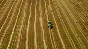 De moderne tractor maakt hooibergen op het gebied na het oogsten Luchtmotiemening stock videobeelden