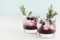 De moderne verfrissende dranken in glazen met ijsblokjes, bosbes, rozemarijn op witte houten raad en pastelkleurmunt kleuren acht royalty-vrije stock afbeelding