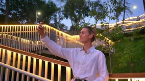 De moderne vrouw bevindt zich op ladder in park, makend selfie op smartphone in avond, het glimlachen, communicatie concept stock videobeelden